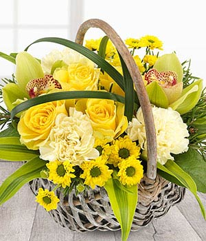 bright yellow flower basket with orchids roses and