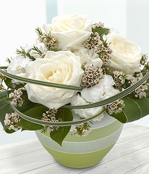 white roses carnations and wax flower in container